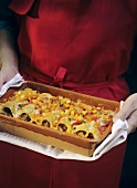 Woman in red apron holding baking dish of cannelloni