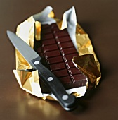 Bar of chocolate in gold foil with knife