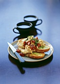 Spicy scrambled egg with chorizo on toasted bread; coffee