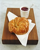 Croissant on paper napkin; strawberry jam