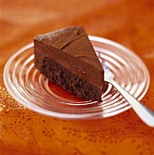 Piece of chocolate cream cake on glass plate