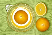 Oranges on lemon squeezer on green wooden background