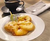 Apple fritters with sugar; cup of coffee