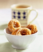Donuts with sugar in white bowl in front of coffee cup