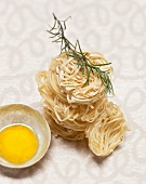Egg yolk, pasta nests and sprig of rosemary