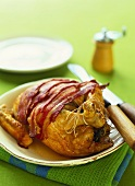 Roast chicken with slices of bacon