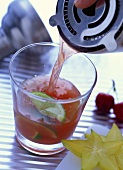 Cocktail with cherry juice and lime wedges