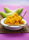 Diced mango in bowl in front of slices of melon