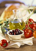 Still life with olives, tomatoes, olive oil and bread