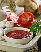 Tomato sauce in bowl, surrounded by ingredients