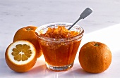 Orange marmalade in a glass dish and Seville oranges