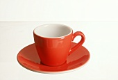 A red coffee cup with saucer