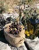 Eine Flasche Olivenöl, Nizzaer Oliven in einer Holzschale