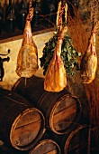 Air-dried ham hanging above wooden barrels