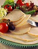Sliced turkey breast with salad on plate