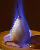 Eine Birne auf Teller wird flambiert