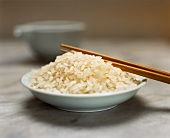 Sushi rice in a bowl with chopsticks