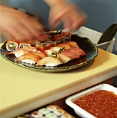 Hand laying sushi on a plate