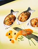 Three bowls of salmon tartare, salmon fillet on knife