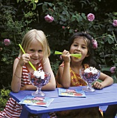 Two girls eating berry dessert out of sundae glasses