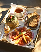 Breakfast Tray with Prosciutto, Melon, Soft Boiled Egg, Bread and Tea