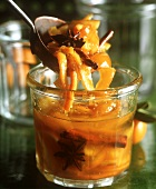 Orange and kumquat jam in a jar and on a spoon