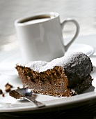 A piece of chocolate cake, a cup of coffee behind