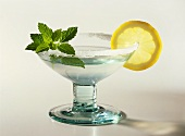A glass of Margarita cocktail with mint leaves