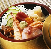 Chirashi-Sushi mit gemischtem Fisch im Bambuskörbchen