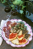 Plate of antipasti with bruschetta, crostini, sausage