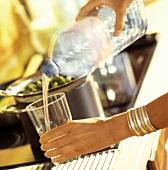 Mineralwasser aus Plastikflasche ins Glas eingiessen