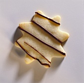 A biscuit decorated with chocolate stripes