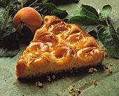 A piece of apricot tart, a fresh apricot beside it