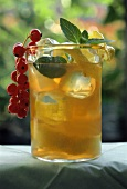 A glass of iced tea with mint leaves and redcurrants