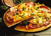 A salami pizza, cut into