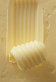 A piece of butter with butter curls (close-up)