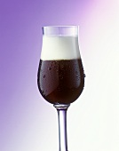 A glass of White Russian with a lot of froth