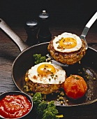 Rissole with fried egg and tomato in frying pan