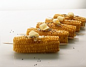 Grilled corn cobs with butter curls