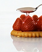 Pouring cake glaze over strawberry tartlet
