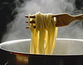 Lifting spaghetti out of steaming pan with wooden fork