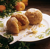 Two apricot dumplings with breadcrumbs, one opened