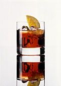 A glass of Campari with ice cubes and lemon slice
