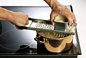 Making noodles (Spaetzle): shaving dough into boiling water