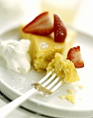 A piece of lemon cake with strawberries and cream
