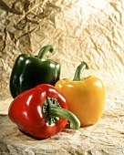Three peppers (red, yellow, green) on paper