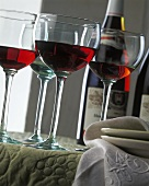 Drei Gläser Rotwein, dahinter Rotweinflasche