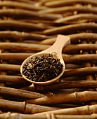 Dried tea leaves on a wooden spoon