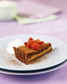 A piece of chocolate toffee tart, decorated with raspberries