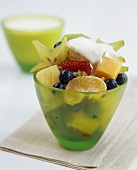 Fruit salad with a blob of cream in green glass bowl